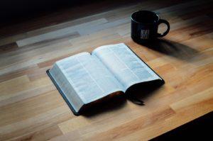 opened book beside black ceramic mug
